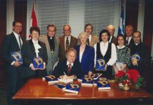 L'historien Michel Pratt procède au lancement du premier Dictionnaire historique de Longueuil en 1995. On remarque Mgr Bernard Hubert et le curé Raymond Poisson.